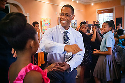 """Teaching artist Derrick Evans invites Tiana Sookram to dance.  Students of Dancing Classrooms of the Virgin Islands dance at a reception for their parents, family community, and school partners at the Virgin Islands Council on the Arts.  Students spent weeks learning the Tango, Foxtrot, Meringue, Swing, Rumba, and Waltz that will culminate in """"Colors of the Rainbow"""" team match competition at Reichhold Center for the Arts on Saturday, May 9, 2015.  St. Thomas, USVI.  8 May 2015.   © Aisha-Zakiya Boyd"""