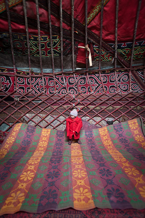 A young Kyrgyz boys is kept warm indoor while the yurt is being prepared for the summer season...Daily life at the Khan (chief) summer camp of Kara Jylga...Trekking through the high altitude plateau of the Little Pamir mountains (average 4200 meters) , where the Afghan Kyrgyz community live all year, on the borders of China, Tajikistan and Pakistan.