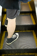 a person in shorts with hairy legs standing on a escalator