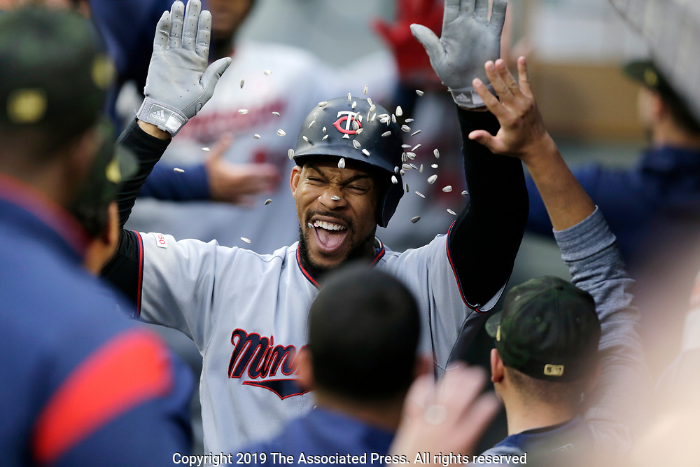 Minnesota Twins' Byron Buxton is showered with sunflower seeds as he celebrates in the dugout after hitting a grand slam against the Seattle Mariners during a baseball game, Saturday, May 18, 2019, in Seattle. (AP Photo/John Froschauer)