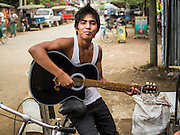 11 NOVEMBER 2014 - SITTWE, MYANMAR: A teenager plays his guitar on the street in Sittwe. Sittwe is a small town in the Myanmar state of Rakhine, on the Bay of Bengal.   PHOTO BY JACK KURTZ