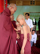 A monk helps a novice put on his robes for the first time during a Shinbyu Novice Ceremony on 25th March 2016 in Loikaw, Kayah State, Myanmar. In Myanmar, it is customary for boys to enter the monastery as a Buddhist novice between the age of ten and 20 years old although they can be as young as four, for at least one week.