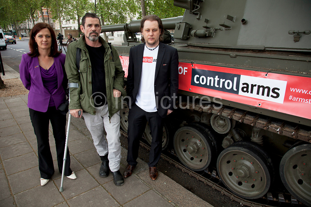 Spokespeople Anna Macdonald and Oliver Sprague with injured war photographer Paul Conway. Campaigners and supporters from Oxfam and Amnesty International, as part of the Control Arms coalition, drive an Abbot gun tank around central London to highlight the need for a global Arms Trade Treaty (ATT) to be agreed during a United Nations conference next month (July 2012). London, England, UK. 27th June 2012.