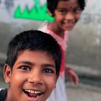 Asia, India, Calcutta. A young boy pops into frame while photographing a local Calcutta girl.