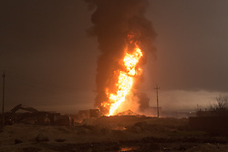 Licensed to London News Pictures. 08/11/2016. Qayyarah, Iraq. Machinery, apparently being used to try and extinguish burning oil facilities, is seen in the Iraqi town of Qayyarah, Iraq. Oil wells in and around the town of Qayyarah, Iraq, we set alight in July 2016 by Islamic State extremists as the Iraqi military began an offensive to liberated the town.<br /> <br /> For two months the residents of the town have lived under an almost constant smoke cloud, the only respite coming when the wind changes. Those in the town, despite having been freed from ISIS occupation, now live with little power, a water supply tainted with oil that only comes on periodically and an oppressive cloud of smoke that coats everything with thick soot. Many complain of respiratory problems, but the long term health implications for the men, women and children living in the town have yet to be seen. Photo credit: Matt Cetti-Roberts/LNP