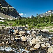 preston park woman backpacker crossing siyeh creek glacier national park