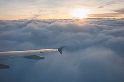 Aerial view of airplane flying over clouds at sunset