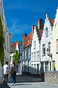 Couple photographing painted houses with crow-stepped gables by Peerdenstraat and Groenerei (green Canal) in Bruges, Belgium