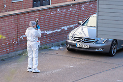 © Licensed to London News Pictures. 22/04/2021. Walton-on-Thames, UK. A forensic investigator takes a photograph of a car inside the cordon at the scene behind a row of shops. Police responded to an incident at 14:15 BST on Church Street in Walton-on-Thames, police and forensic investigators could be seen at the scene. Photo credit: Peter Manning/LNP