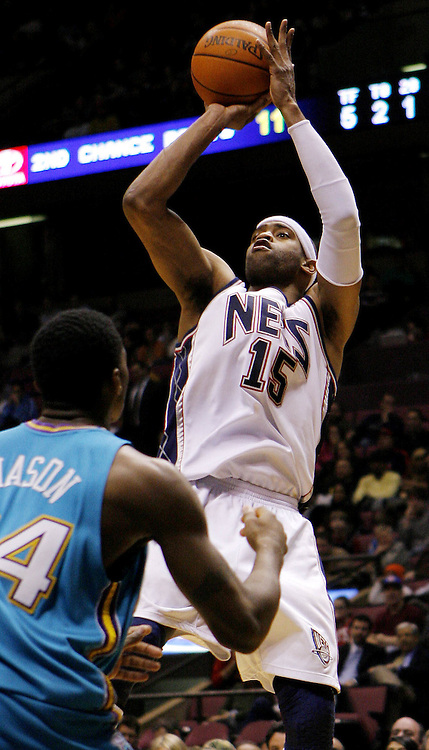The Nets' Vince Carter (R) shoots over the Hornets' Desmond Mason (L) during the second half of the New Orleans/Oklahoma City Hornets' 111-107 victory over the New Jersey Nets at Continental Airlines Arena in East Rutherford, New Jersey on Wednesday 21 February 2007.