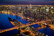 Aerial photograph of Roosevelt Island and Manhattan from a helicopter at night by photographer Evan Joseph.