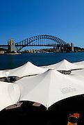 Umbrellas on the Sydney Opera House concourse, with the Sydney Harbour Bridge in background. Sydney, Australia
