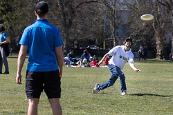 © Licensed to London News Pictures. 18/04/2021. London, UK. A man throws a frisbee during sunny weather in Greenwich Park in South East London. Temperatures are expected to rise with highs of 16 degrees forecasted for parts of London and South East England this week . Photo credit: George Cracknell Wright/LNP