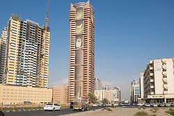 View of street and high-rise modern buildings in Ajman emirate in United Arab Emirates
