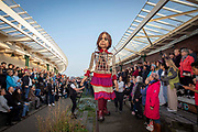 Little Amal took her first steps in the United Kingdom today when she arrived to a warm welcome from locals on the 19th of October 2021 at the Harbour Station in Folkestone, United Kingdom.  Little Amal is a 3.5 metre-tall living artwork of a young Syrian refugee child who has spent the last 3 months walking 8000 km from the boarder of Syria across Turkey, Greece, Italy, France, Switzerland, Germany, Belgium and the UK to focus attention on the urgent needs of young refugees.
