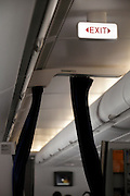 lighted up emergency exit sign inside a passenger airplane with class dividing curtain