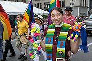 A woman wears a clerical collar and a rainbow liturgical stole.