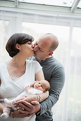 Parents kissing each other and cradling newborn baby girl in their arms, Munich, Bavaria, Germany