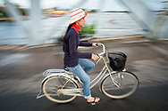 A Local Cambodian girl cycling over the old bridge in Kampot, Cambodia