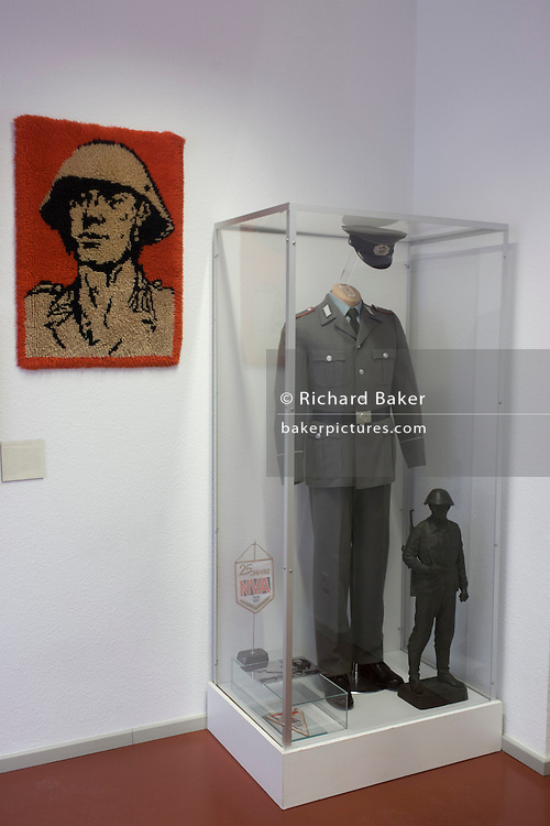 A soldier in uniform, an exhibit in 'Haus 1' the ministerial headquarters of the Stasi secret police in Communist East Germany, the GDR. Built in 1960, the complex now known as the Stasi Museum. Before the fall of the Wall, it was a 22-hectare complex of espionage whose centrepiece is the office and working quarters of the former Minister of State Security, Erich Mielke who considered their role as the 'shield and sword of the party', conducting one of the world's most efficient spying operations against its political dissenters during its 40-year old socialist history. Between 1950 and 1989, the Stasi employed a total of 274,000 people in an effort to root out the class enemy. During Hitler's Third Reich, the Gestapo had one agent for every 2,000 citizens whereas the Stasi had approximately an spy for every 6.5. Here at the Stasi HQ alone 15,000 were employed plus the many regional stations. German media called East Germany 'the most perfected surveillance state of all time' - administered from this complex of offices.
