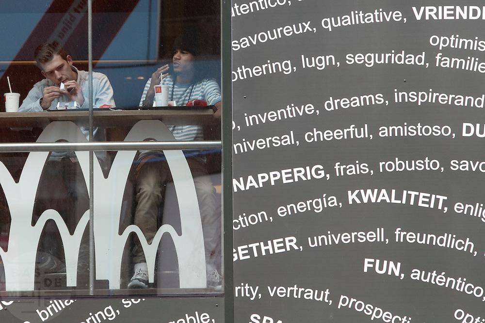 Twee mannen zitten bij de vernieuwde McDonalds aan de Lange Viestraat in Utrecht.<br /> <br /> Two men are eating at a McDonalds restaurant in Utrecht.