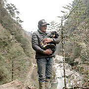 A man holds his dog The dog's name is Sonam. On the trek going from Laya village to the beginning of the drivable road.