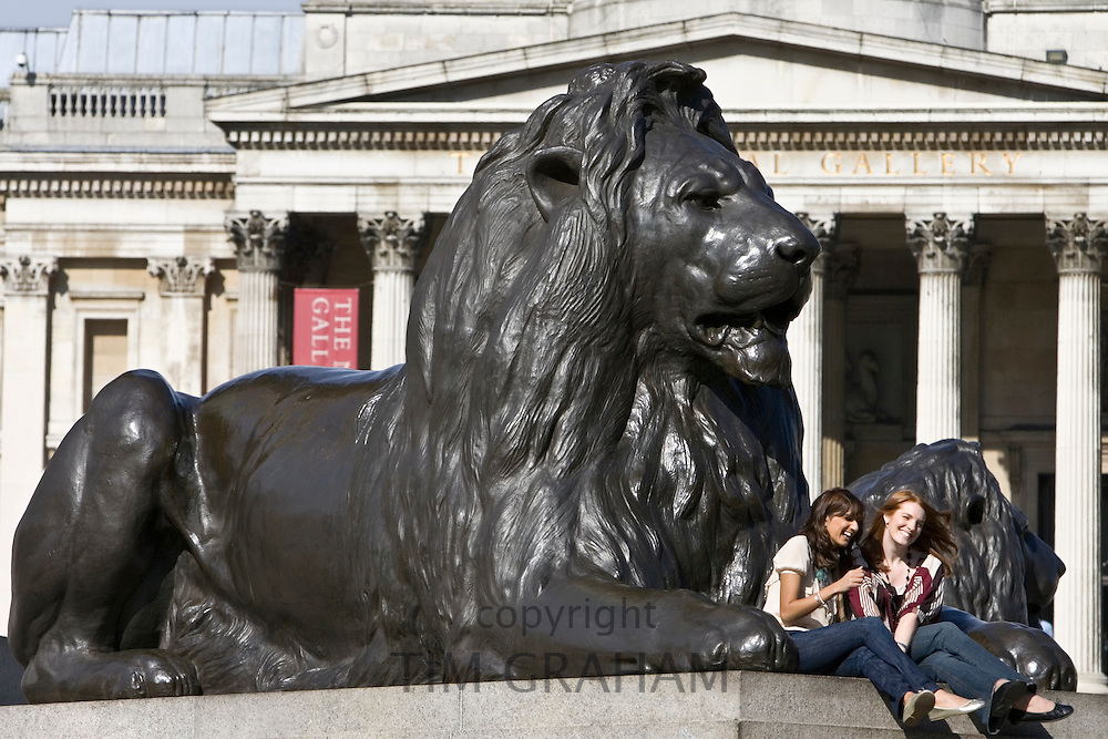 Tourists sit on lion statues in front of National Gallery in Trafalgar Square, London, United Kingdom