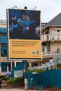 Rwanda. Giterama. Large hoarding advert for MTN mobile money ( money through cell phone) showing a couple looking at a phone as they transfer money, with text in Kinyarwanda. A man on a nearby balcony chats on his phone and two men underneath it talk to eachother.