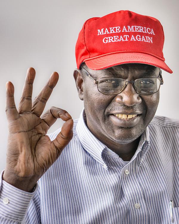 Barack Obama's brother Malik wearing a Make America Great Again making the okay sign