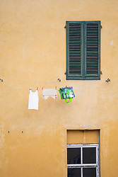 Laundry hanging on clothesline against house wall, Lucca, Tuscany, Italy