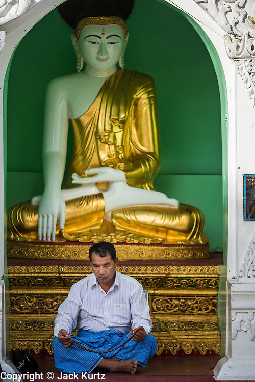 07 JUNE 2014 - YANGON, YANGON REGION, MYANMAR: A man prays in front of a statue of the Buddha at Shwedagon Pagoda in Yangon (Rangoon), Myanmar (Burma). Shwedagon Pagoda is officially called Shwedagon Zedi Daw and is also known as the Great Dagon Pagoda and the Golden Pagoda. It's a 99 metres (325ft) gilded pagoda and stupa located in Yangon. It is the most sacred Buddhist pagoda in Myanmar with relics of the past four Buddhas enshrined within: the staff of Kakusandha, the water filter of Koṇāgamana, a piece of the robe of Kassapa and eight strands of hair from Gautama, the historical Buddha.   PHOTO BY JACK KURTZ