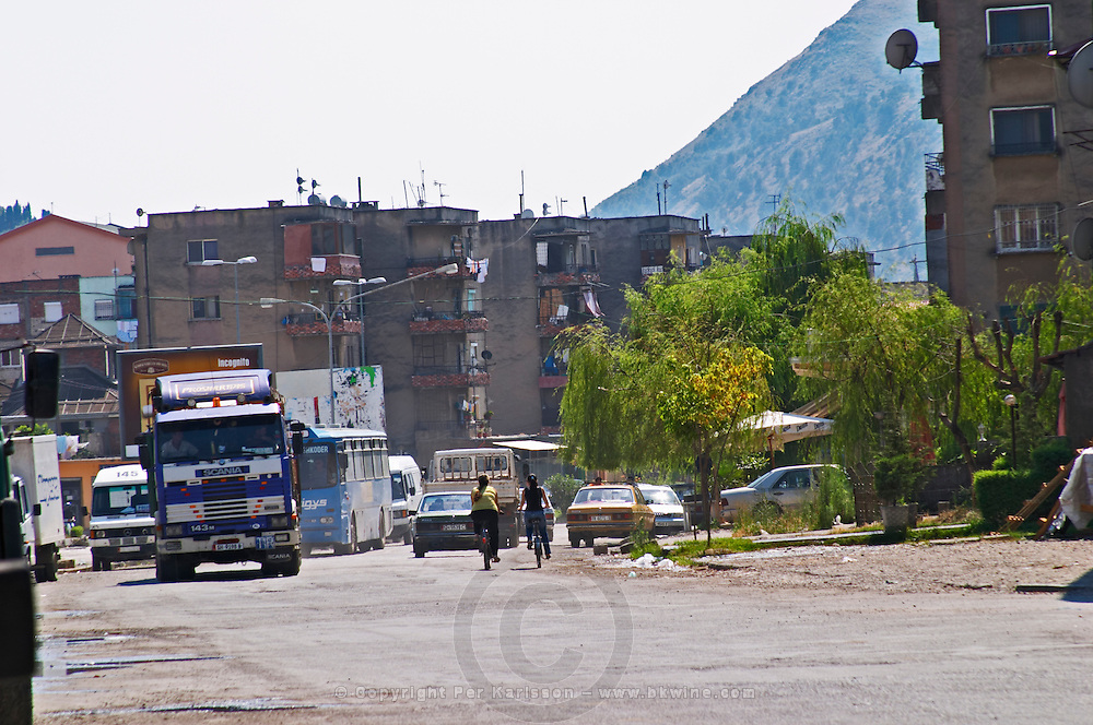 The street in front of the restaurant - typical Shkodra street with pot holed road, apartment buildings, heavy lorries trucks and busses. Tradita traditional restaurant, Shkodra. Albania, Balkan, Europe.