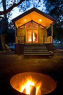 Evening campfire in fire pit in front of rustic wood cabin, El Capitan Canyon Resort, near Santa Barbara, California