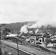 """0904-D45 The East Side Mill & Lumber Company before 1925, when six of the support columns of the Sellwood bridge were built through this complex. Train tracks are now the Springwater corridor bike path. """"The East Side Lumber Company was established in 1902, on the site of the smallerSorensen and Young Planing Mill, in operation since the 1890s. During the first decade ofthe 20th century, the mill thrived in this growing, lumber-hungry city, expanding toinclude door- and box-making subsidiaries. In the 1920s, the complex employed 300-500men, many of whom lived in Sellwood. Timber was hauled in by interurban railroad, orfloated in on the river. Hard times in the 1930s led to the East Side Lumber Company's downfall. By the end ofthe decade, the main mill had shut down. In 1940, a huge fire burned many of thebuildings. One part of the complex, the Oregon Door Company, stayed in business untilthe 1950s. The first Sellwood Bridge was designed to cross at the site of the East Side Lumbercomplex. In fact, the Oregon Door Company was right in its path. Multnomah Countycouldn't afford to purchase and demolish the building, so engineers built six of the bridgecolumns through it. This unusual building stood until 2011."""