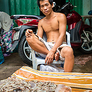 Vietnamese man selling seafood at market in Ho Chi Minh City