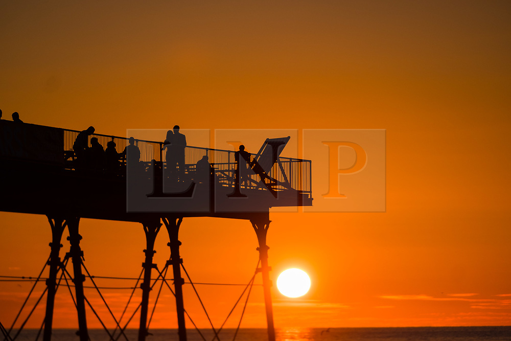 © Licenced to London News Pictures. <br /> Aberystwyth Wales UK, Wednesday 25 July 2018. UK Weather: People  are silhouetted by the glorious setting sun over Aberystwyth pier at the end of a day of hot summer sunshine.  The UK wide heatwave continues, with little respite from the very dry weather  despite some rain in the forecast for the weekend. hoto credit: Keith Morris / LNP