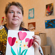 CAPTION: Lybov proudly holds a design that her son Erik, born with multiple severe disabilities, made for her. There are plenty more on the wall behind her, testimony to the special bond that the two have. LOCATION: St Petersburg, Russia. INDIVIDUAL(S) PHOTOGRAPHED: Lybov Chusheva.