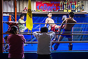 23 DECEMBER 2014 - BANGKOK, THAILAND:  People from the neighborhood watch boxers spar at the Kanisorn gym in Bangkok. The Kanisorn boxing gym is a small gym along the Wong Wian Yai - Samut Sakhon train tracks. Young people from the nearby communities come to the gym to learn Thai boxing. Muay Thai (Muai Thai) is a mixed martial art developed in Thailand. Muay Thai became widespread internationally in the twentieth century, when Thai boxers defeated other well known boxers. A professional league is governed by the World Muay Thai Council. Muay Thai is frequently seen as a way out of poverty for young Thais. Muay Thai professionals and champions are often celebrities in Thailand.    PHOTO BY JACK KURTZ