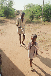 Young boy using stick to guide Indian man with visual impairment along road,