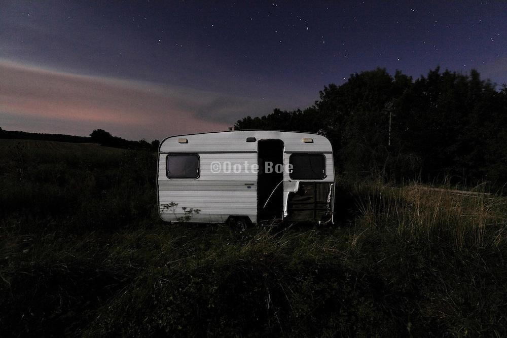 old falling apart caravan during a full moon night