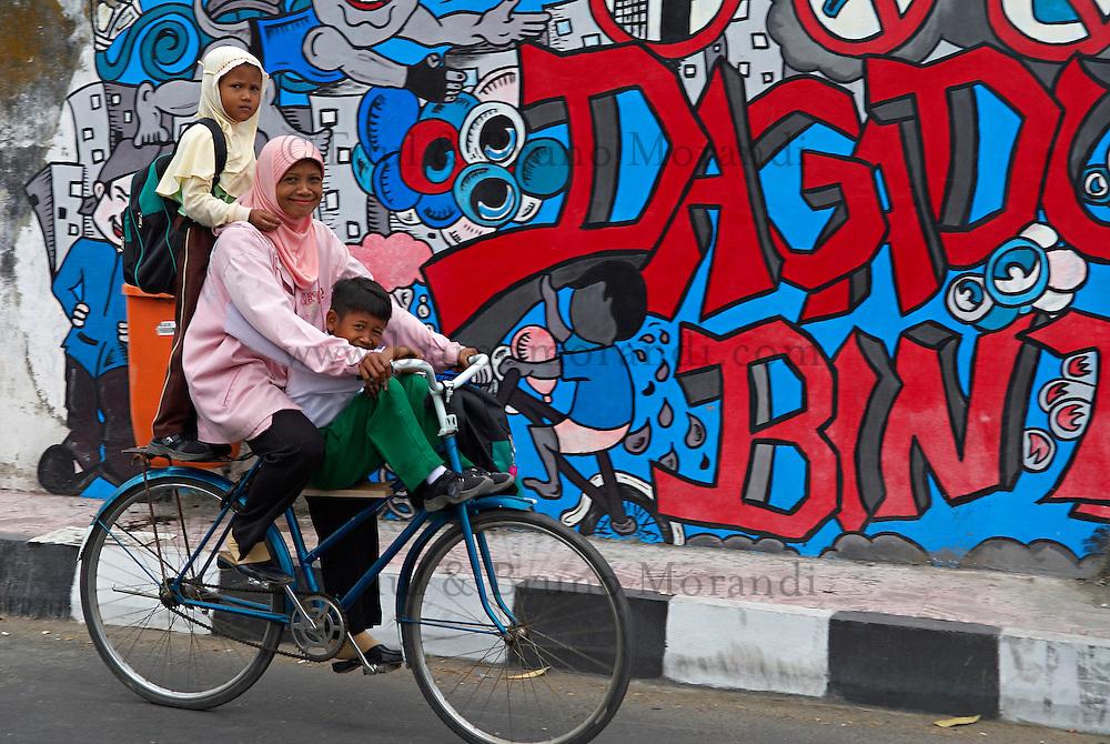 Indonesie. Île de Java. Yogyakarta. Transport des enfants pour l'école. // Indonesia. Java island. Yogyakarta. Family on the way to school.