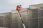 Maintenance of the Vertical Agriculture hangars at Sky Greens<br /><br />Sky Greens is a pioneering adventure in vertyical farming, one of the first of its kind, founded by Daniel Chea.<br /><br />As written in their website:<br /><br />World's first low carbon hydraulic water-driven, tropical vegetable urban vertical farm, using green urban solutions to achieve enhanced green sustainable production of safe, fresh and delicious vegetables, using minimal land, water and energy resource<br /><br />Locally grown vegetables in Singapore currently constitute only 7% of local consumption. Demand for local vegetables exceeds supply. Singaporeans trust the quality, freshness and safety of local vegetables, grown using good agricultural practice under the supervision of the Agri-Food & Veterinary Authority of Singapore.<br /> <br /> The A-Go-Gro vertical systems which are 9m in height (3 storeys), housed in protected-outdoor green houses, allow tropical leafy vegetables to be grown all year round at significantly higher yields (than traditional growing methods) that are safe, of high quality, fresh and delicious.<br /><br />Green urban technologies are used on the farm, which is easy and environmentally friendly to operate and maintain. Patented low carbon hydraulic water-driven green technology. Soil-mix, fertilizers and water are controlled. Modular A-frame structures for easy installation & maintenance. Outdoor green houses, which use abundant sunlight in the tropics throughout the year. Green technology is used to achieve the 3R ( reduce, reuse and recycle)