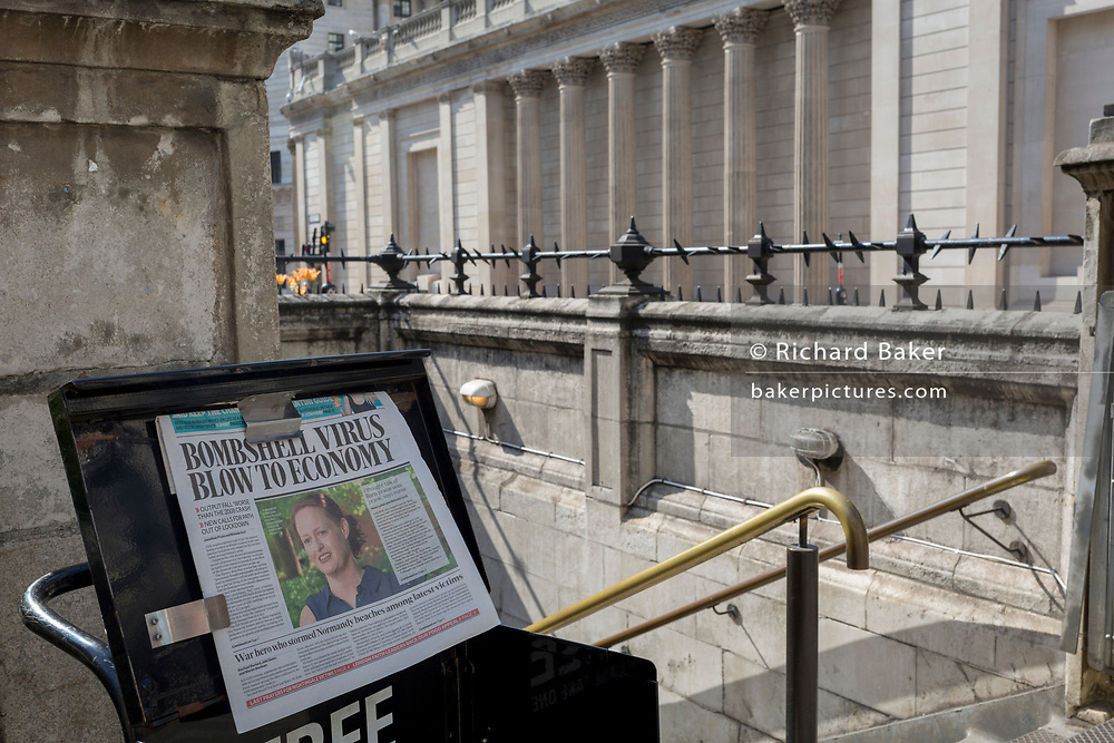 As the UK government's lockdown restrictions during the Coronavirus pandemic continues, and number of UK reported cases rose to 138,078 with a total now of 18,738 deaths, Jenny McGee, a New Zealand-born ICU nurse who treated PM Boris Johnson while in intensive care, appears on the front page of the Evening Standard newspaper alongside a bleak economic forecast, outside the Bank of England in a deserted City of London, the capital's financial district, on 23rd April 2020, in London, England.