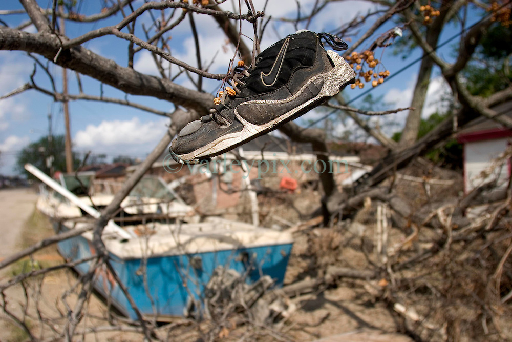 01 October, 05.  New Orleans, Louisiana. Lower 9th ward. Hurricane Katrina aftermath. <br /> The remnants of the lives of ordinary folks, now covered in mud as the flood waters recede. A Nike sneaker hangs in a tree, a washed up boat in the background.<br /> Photo; ©Charlie Varley/varleypix.com