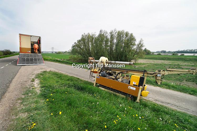 Nederland, Andelst, 23-4-2019In het buurtschap Wolferen is de FUGRO bezig met onderzoek aan de voet van de dijk van de rivier de waal. Doel is vast te stellen hoe dik de bodemlagen van de waaldijk en met name van de kleilaag is.  Het waterschap en de dijkbeheerder meten deze op verschillende plekken om te weten waar zwakke plekken ivm kwelwater zich bevinden zodat die versterkt kunnen worden . Het is geotechnisch onderzoek middels  HPT sondering ( Hydraulic Profiling Tool ). Fugro is een Nederlands bedrijf dat gegevens over het aardoppervlak en de bodem verzamelt en interpreteert.Foto: Flip Franssen.