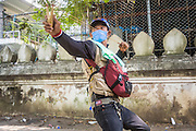 02 DECEMBER 2013 - BANGKOK, THAILAND: An anti-government protestor uses a slingshot to shoot rocks at police positions near Government House in Bangkok. Anti-government protestors and Thai police continued to face off Monday for a second day. Police used tear gas, water cannons and rubber bullets against protestors who charged their positions near the barriers on Chamai Maruchet bridge on Phitsanulok Road, which leads to the Government House.     PHOTO BY JACK KURTZ