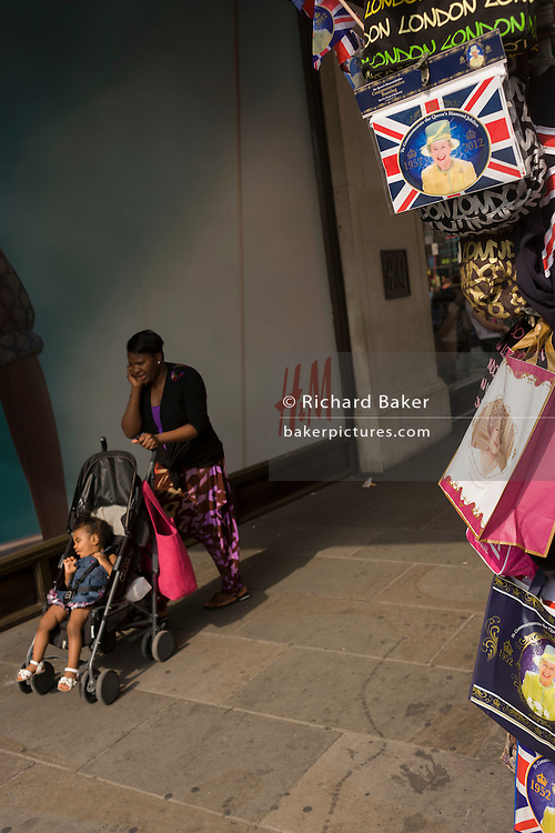 A mother and child passes royal souvenir merchandise in Oxford Street in the week of a smiling Queen's diamond Jubilee celebrations.