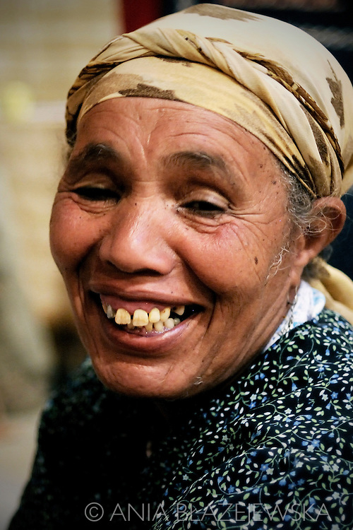 Morocco, Ait Benhaddou. Portrait of a smiling Berber woman working in a carpet workshop.