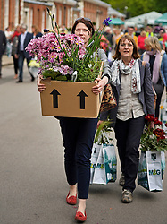 © London News Pictures. 23/05/2015. London, UK. Members of the public carry exhibitors' plants from the 2015 Chelsea Flower show, which ends today (Sat). The Royal Horticultural Society flagship flower show has been held at the Royal Hospital in Chelsea since 1913. Photo credit: Ben Cawthra/LNP