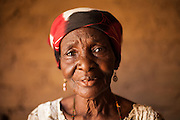 "Delou Ibrahim, 70, poses for a photograph at her home in Saran Maradi, Niger. <br /> Delou Ibrahim has four children and suffered the loss of nine. She has about 40 grandchildren, 16 of which live with her. <br /> ""I've seen several crises. The famine in 1984 was the hardest. Rains were very weak. The stems of millet came out but the spikes gave no grain - nothing,"" she recalls. ""Two years ago at least there were people who harvested millet, but this year the crops have been worse because of the drought and the leaf miners."" Delou's last crop was 30kg, which only provided food for about two days.<br /> Delou and her family receive cash from CARE. ""I get to buy cereal to feed my family, particularly my grandchildren."" They have two daily meals, porridge in the morning and sorghum paste in the evening."